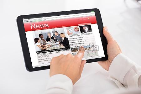 osoba czytajace wiadomosci na cyfrowym tablecie