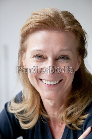 portret usmiechnieta kobieta dojrzalym nad szarym