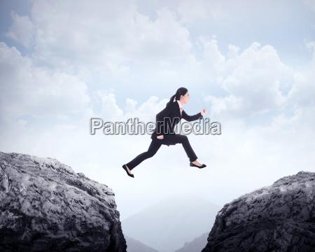 kobieta biznesowych skokow przez wzgorza