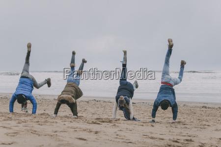 przyjaciele, robi, handstands, na, zimowej, plaży - 23019325