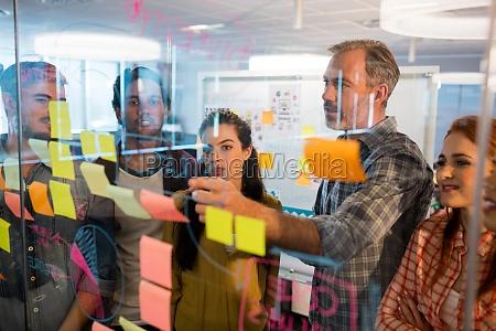 kreatywny zespol biznesowy patrzac na przyklejone