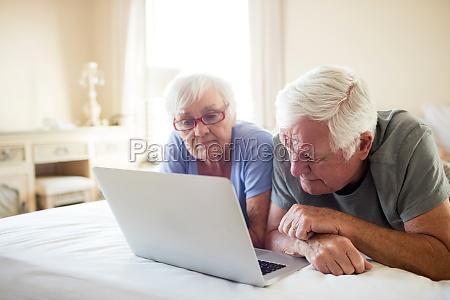 senior couple using laptop on bed
