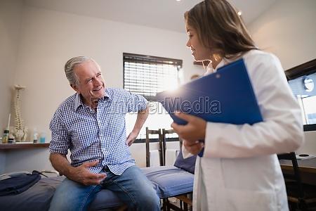 starszy mezczyzna pacjenta pokazujac bol plecow