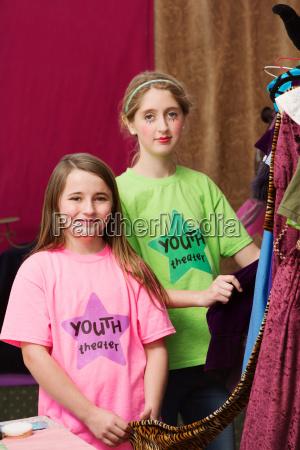 dziewczyny stoja w poblizu kostiumow w
