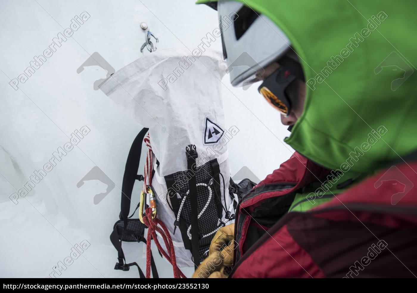 wspinacz, przygotowuje, się, przed, wspinaczką, lodową - 23552130