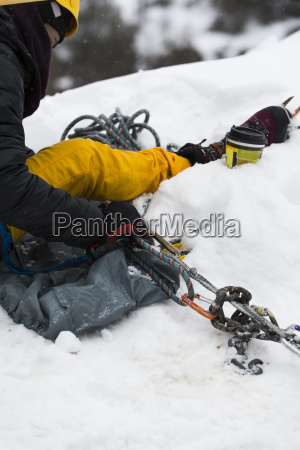 ice climber sitting in snow at