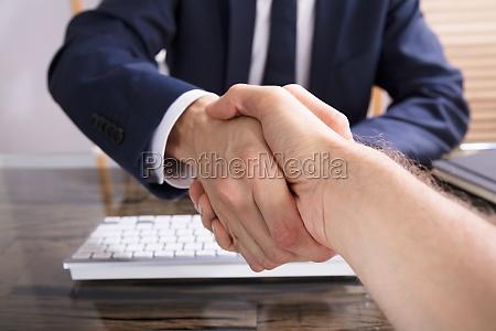 biznesmen potrzasajac reka ze swoim partnerem