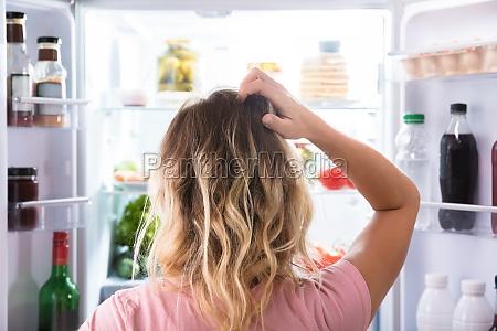 zmieszana kobieta patrzeje w otwartej chlodziarce