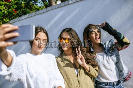trzy usmiechniete mlode kobiety biorace selfie