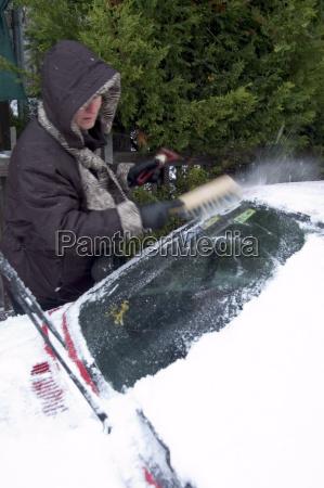 kobieta zwalnia jej samochod z sniegu