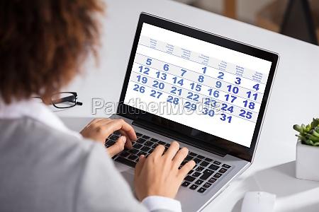 biznesmen patrzac na kalendarz z dzienny