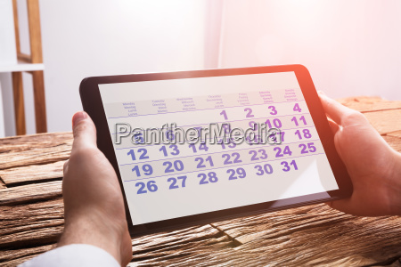 businessperson using calendar on digital tablet