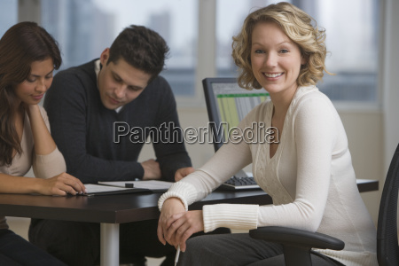 businesswoman at desk with multi ethnic
