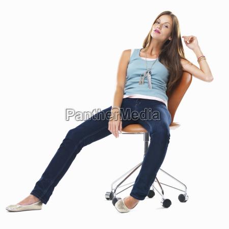 ufna kobieta siedzi swobodnie na krzesle