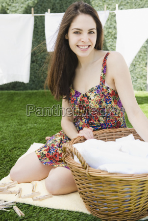 young woman sitting beside a basket