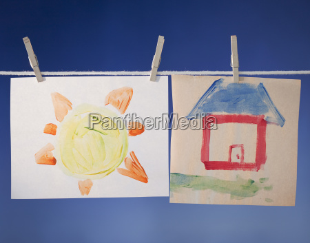 paintings drying on clothesline