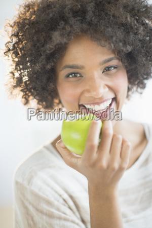 portrait of woman eating apple studio