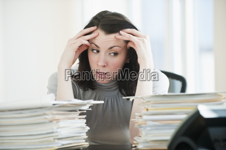 stressed business woman observing paperwork in