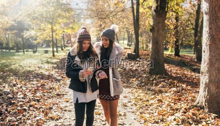 two women with cell phone walking