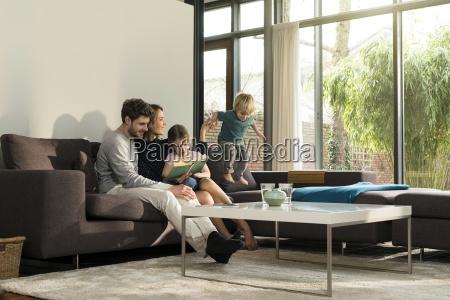 rodzina na kanapie w domu czytanie