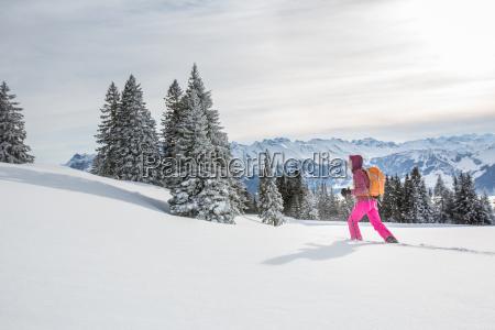 Ladna mloda kobieta rakietach snieznych w