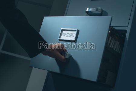pracownik biurowy przeszukujac informacje poufne