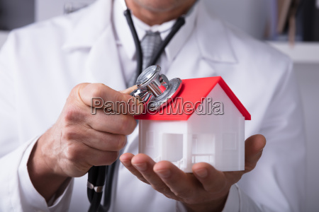 doctor holding stethoscope on house model