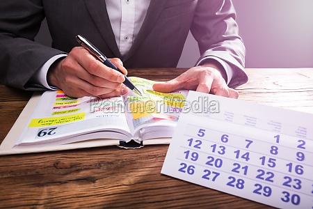 harmonogram sprawdzania rak biznesmena w dzienniku
