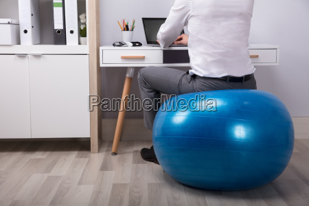 businessperson sitting on fitness ball