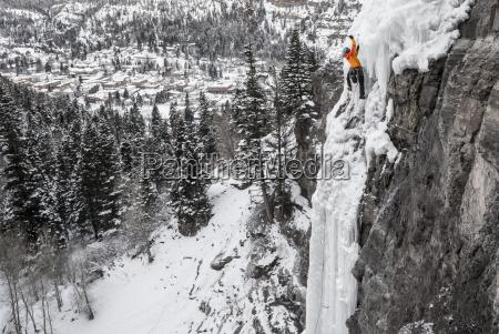 man ice climbing up frozen cascade