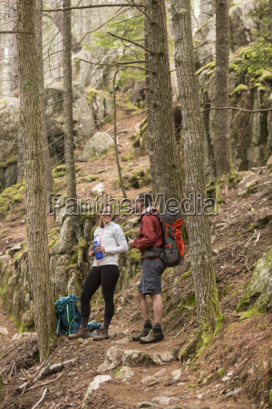 couple resting after walking through forest