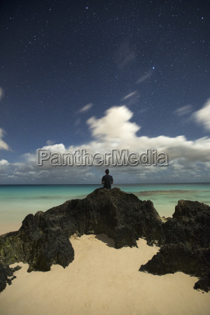 man sitting on rock at beach