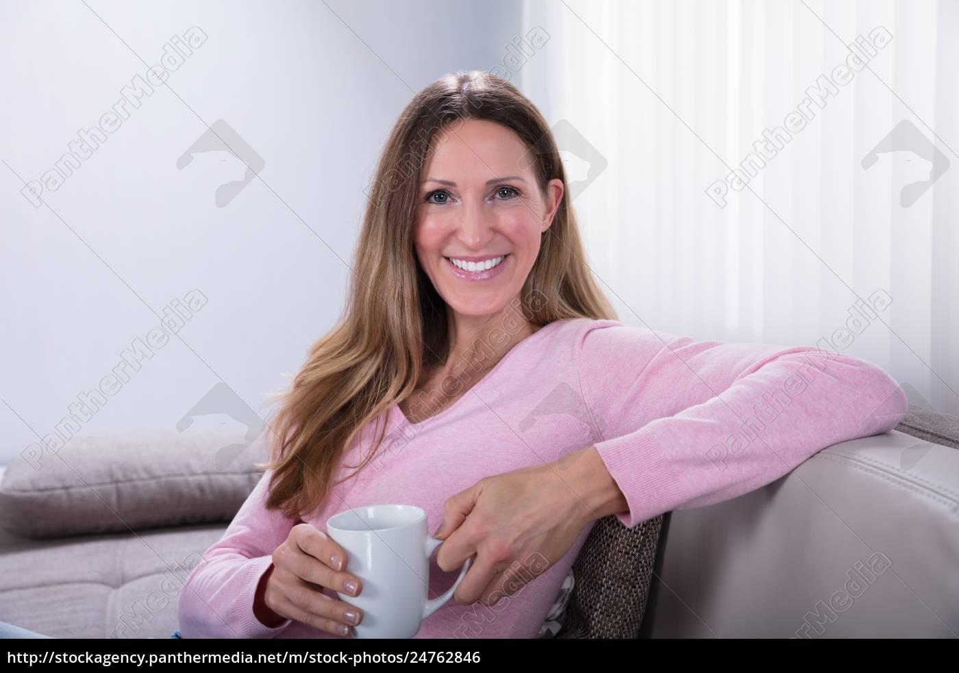 szczęśliwa, kobieta, siedzi, na, kanapie, holding - 24762846
