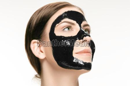 mloda piekna kobieta stosuje maske dla