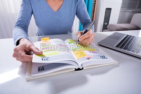 kobieta pisanie harmonogram w kalendarzu dziennik