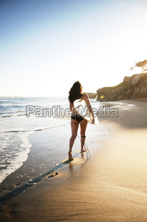 rear view of woman carrying surfboard