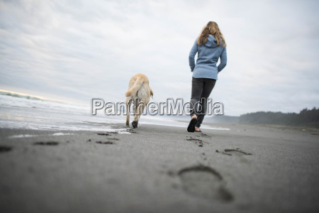 woman with dog walking along beach