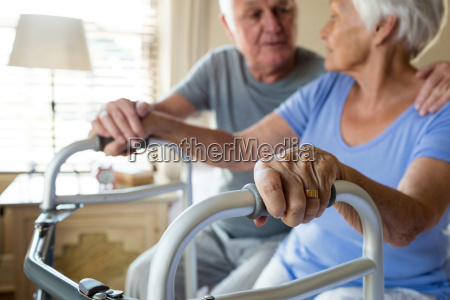 senior man consoling woman in bedroom