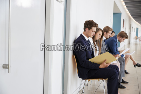 pieciu mlodych kandydatow siedzi czekajac na