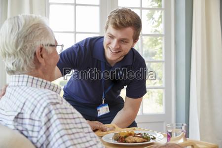 mezczyzna opiekunka sluzacy obiad do starszego