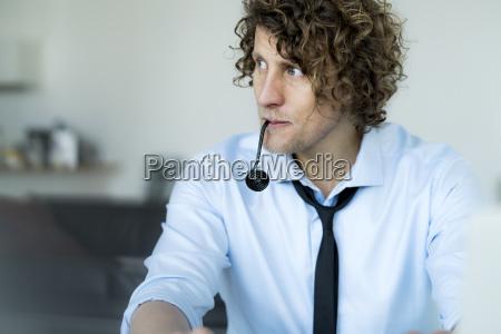 niefrasobliwy biznesmen siedzi w biurze slodycze