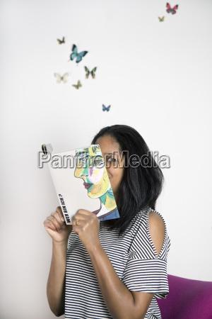 kobieta obejmujaca twarz z ksiazka czytanie