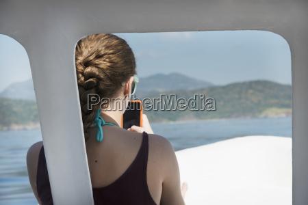mloda kobieta z telefonem komorkowym siedzi