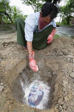 farmer chowa martwy kurczak w bezpieczny