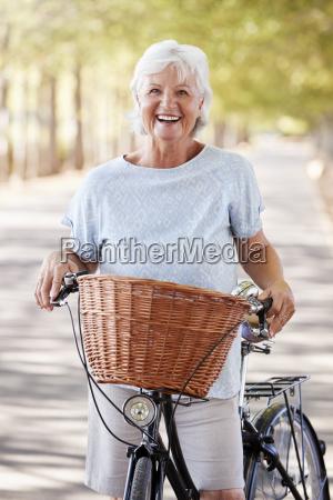 portret usmiechnietej starszej kobiety na rowerze