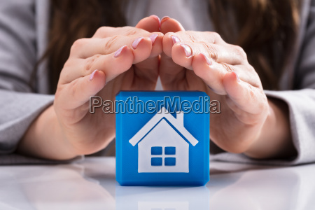 woman protecting cubic block with house