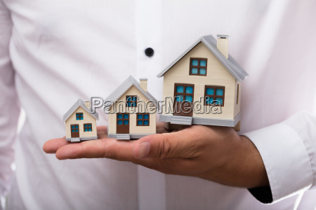 businessman holding increasing size of house
