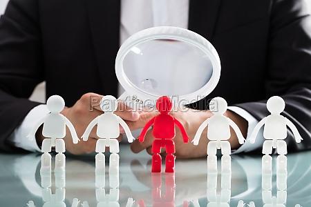 biznesmen patrzac na czerwona figure przez