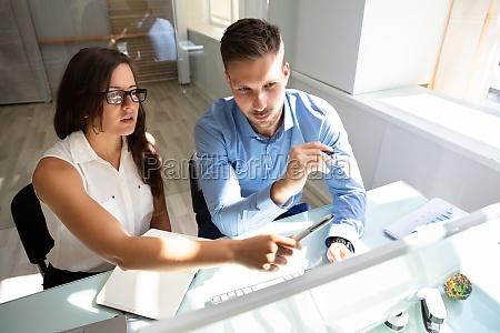dwoch biznesmenow patrzac na komputer majac