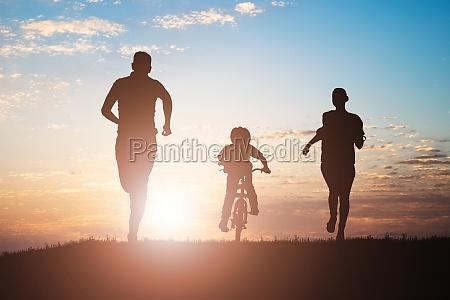 rodzice biegaja z dzieckiem jezdzacym na